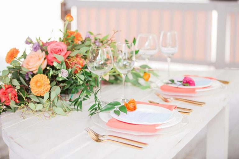 Paradise Cove wedding A Chair Affair farm table coral napkin gold brushed flatware