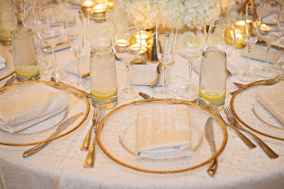 Jewish wedding A Chair Affair gold rim chargers at reception