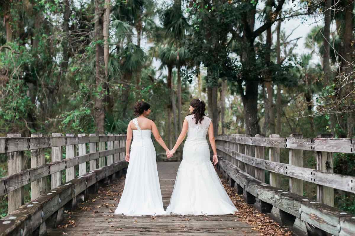 intimate LGBT wedding Reunion Resort A Chair Affair brides on bridge