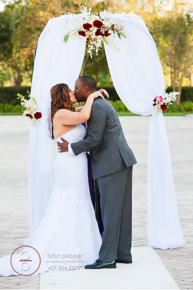 Rosen Shingle Creek Resort Wedding with Ivory and Berry Mary and Brandon Ceremony A Chair Affair garden wedding arch kiss