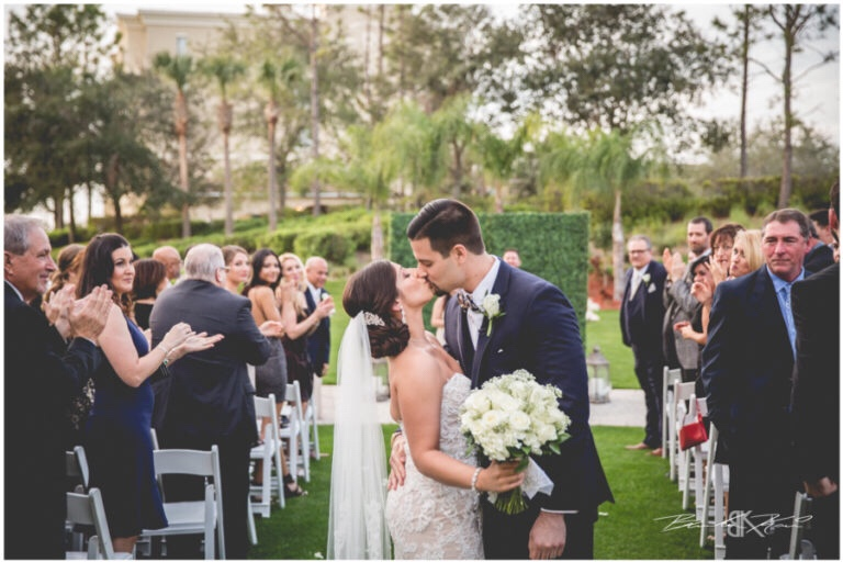 Cream and champagne Orlando wedding Omni Resort at Championsgate Brandon Kari Productions A Chair Affair hedgewood wall kiss at ceremony