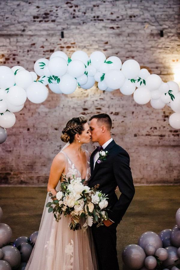 modern whimsical wedding The Rialto a chair affair arch kiss