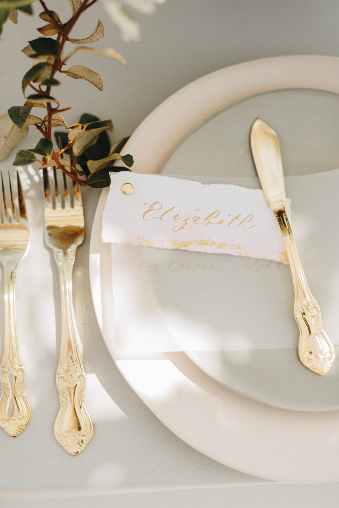 details of place setting with gold baroque flatware